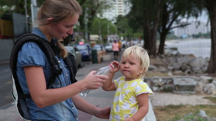 little blonde child drinks water from plastic bottle stand on ba