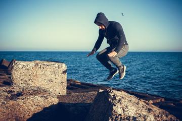 man performs freerunning jump on stones