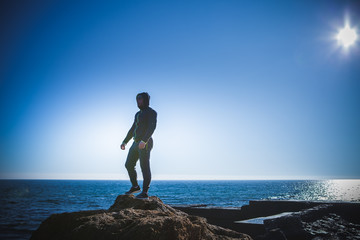 Man stands on a rock by the sea against the sky