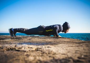 Athlete performing exercises on beach