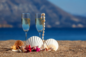 Wines glasses,shells,starfishes on a beach