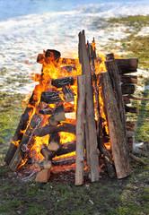 Big campfire, heap of wooden logs burning outdoor