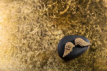 Goldener Hintergrund mit einem Stein und Engel Flügel
