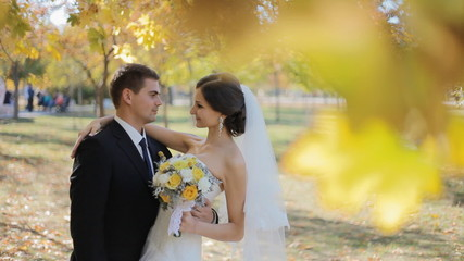 Bride and groom kiss under yellow leaves