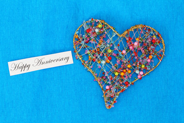 Happy Anniversary card with heart made of colorful beads on blue