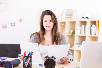 Beautiful young woman working and studying at home