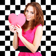 Beautiful young girl with heart in hands on checkered