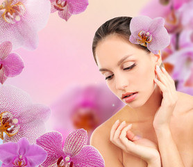 Beautiful young woman with orchid flower in hair