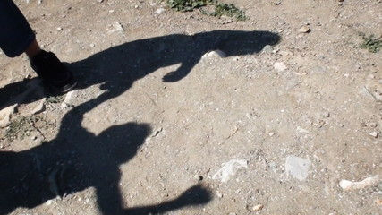 The shadows of two kids fight with each other