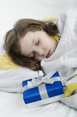 Little girl sleeping in bed with gift