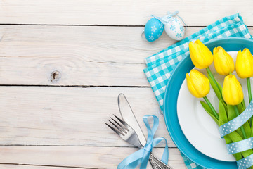 Easter background with yellow tulips and colorful eggs