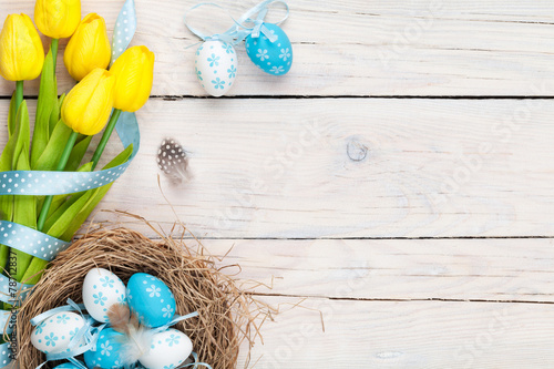 Fotobehang Egg Easter background with blue and white eggs in nest and yellow tu