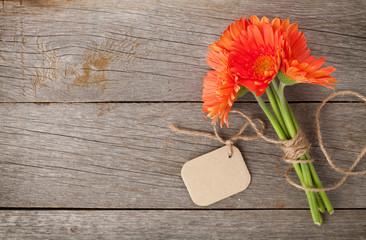 Orange gerbera flowers with tag