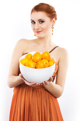 Young red-haired girl with tangerines in evening dress