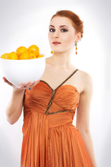 red-haired girl with tangerines in evening dress.