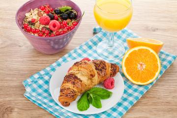Healthy breakfast with muesli, berries, orange juice and croissa