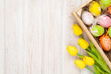 Fototapety Easter background with colorful eggs and yellow tulips