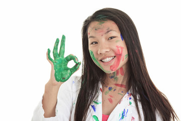 A little asian girl with paint on it isolate on white