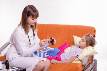 The doctor pours a spoonful of medicine to give sick child