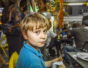 boy enjoys eating at the night market