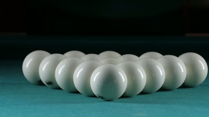 Billiard balls arranged in a triangle. Green table. Slow motion