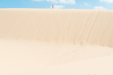 Young woman running on dunes