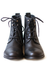 Female pair of black boots with shoelaces tied close up