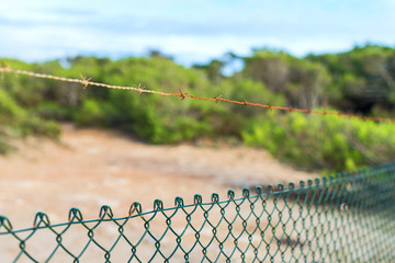 Fence with barbed wire under blue sky.
