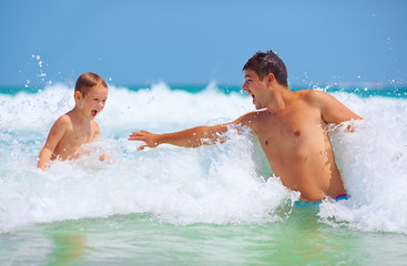 happy father and son jumping in waves, summer vacation