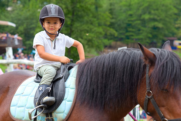 Child learns to ride a horse in a riding school