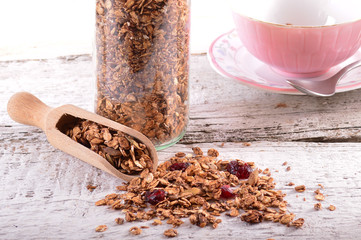 Homemade granola in open glass jar on white wooden background