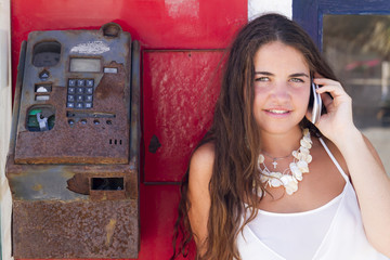 Joven hablando por teléfono junto a una cabina telefónica