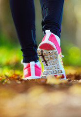 Woman jogging away from camera wearing trainers