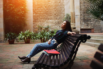 Young woman relaxing on bench and enjoying sunny outdoors