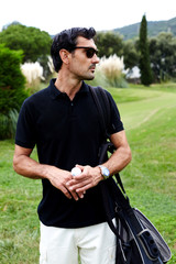 Golf player standing on beautiful course with ball in hands