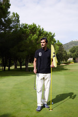 Handsome mature man playing golf at beautiful summer day