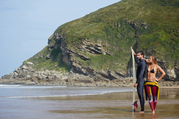 Beautiful surf couple standing on the beach with surfing board