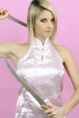 beautiful blond woman holding two ninja swords