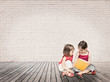little girls reading a book sitting on a wood floor