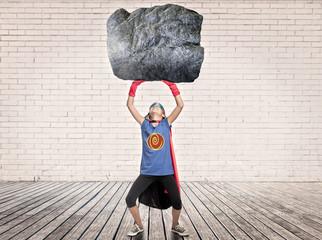 little girl wearing a superhero costume holding a heavy rock
