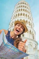 Happy young woman with map in front of leaning tower of pisa