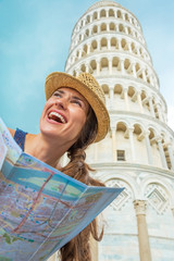 Young woman with map in front of leaning tower of pisa, tuscany