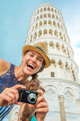 Portrait of happy young woman with photo camera in Pisa