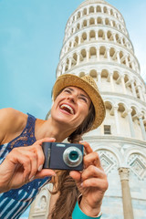 Happy young woman with photo camera in front of tower of Pisa