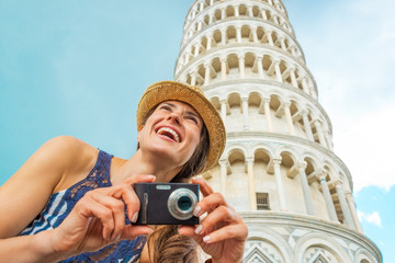 Happy young woman with photo camera in Pisa