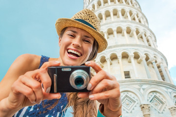 Portrait of smiling young woman with photo camera in Pisa