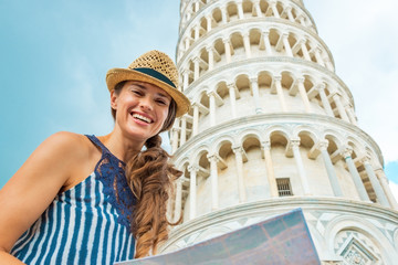 Portrait of happy young woman with map in front of tower of pisa