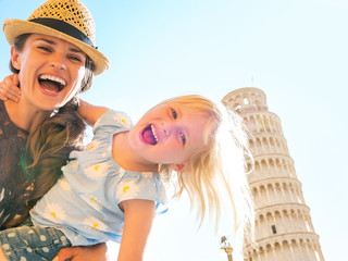 Portrait of mother and baby girl in front of tower of Pisa