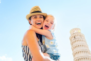 Happy mother and baby girl hugging in front of tower of Pisa