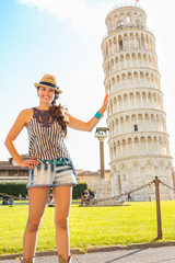 Funny young woman supporting leaning tower of pisa, tuscany